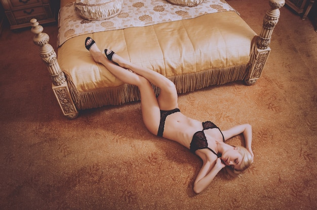 Sexy mädchen in dessous posiert im hotelzimmer. schönheit und mode