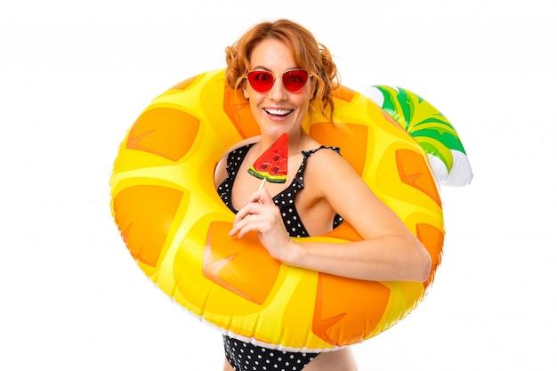 Sexy mädchen in einem badeanzug in einem schwimmkreis in form von ananas im urlaub auf einem weißen