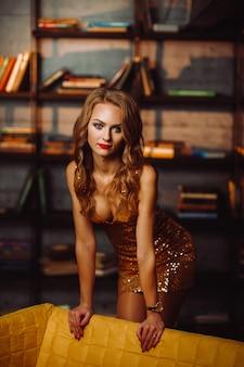 Sexy mädchen in einem goldenen kleid auf dem hintergrund der bücher in der bibliothek. modell mit langen haaren und rotem lippenstift im innenraum.