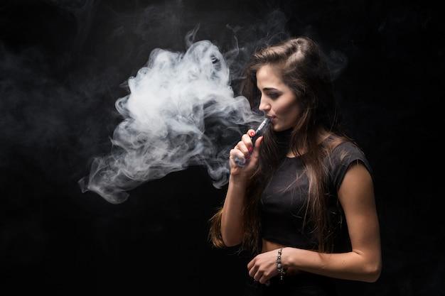 Sexy mädchen in einem schwarzen kleid, das elektronische zigarette auf dunkler wand raucht