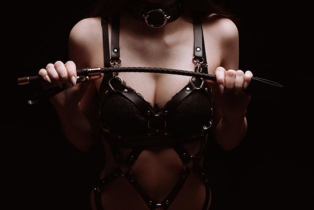Sexy mädchen in einem schwarzen schönen bh, der mit einer peitsche spielt. das konzept des bdsm