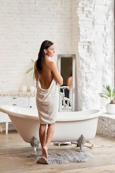 Sexy mädchen in einem weißen kittel ist im begriff, ein bad zu nehmen. mädchen im bademantel nach dem baden.