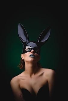 Sexy mädchen in einer schwarzen häschenmaske
