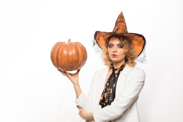 Sexy mädchen in halloween-kostümhexe mit kürbisfeier-herbstfeiertags-süßes oder saures