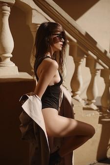 Sexy mädchenmodell mit einer perfekten verführerischen figur in einem body und einem regenmantel posiert an einem sonnigen tag auf der straße