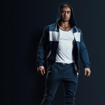 Sexy männliches fitnessmodel mit offenem sweatshirt auf dunklem hintergrund