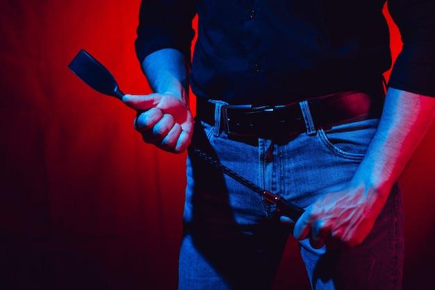 Sexy mann hält eine peitsche auf einem roten