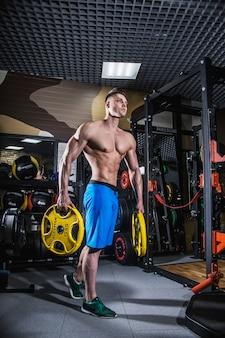 Sexy mann im fitnessstudio mit hanteln. sportlicher mann mit großen muskeln und breitem rücken trainiert im fitnessstudio