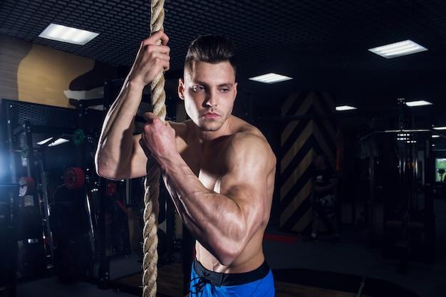 Sexy mann in der turnhalle mit dummköpfen. sportlicher mann mit großen muskeln