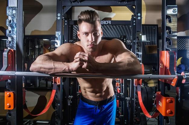 Sexy mann in der turnhalle mit hanteln. sportlicher mann mit großen muskeln und breitem rücken trainiert im fitnessstudio, fitness und aufgepumpter bauchpresse. russland, swerdlowsk, 2. juni 2018