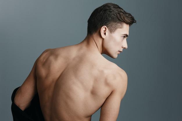 Sexy mann mit einem nackten rücken schaut zur seite auf einer grauen hintergrundrückansicht eines fitness-sports. hochwertiges foto