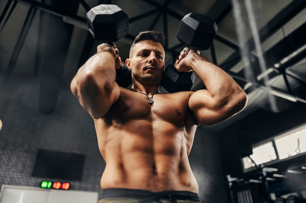 Sexy mann mit nacktem oberkörper, der mit beiden händen schwere hanteln in der dunklen atmosphäre eines sportlers hebt