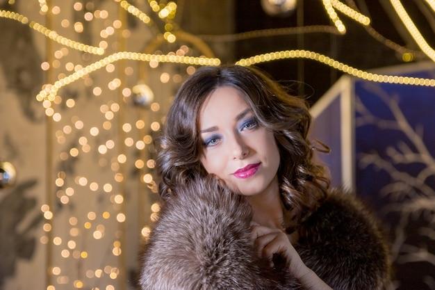 Sexy modefrau, die im winterpelzmantel trägt. junge frau im pelzmantel mit den roten lippen steht an der messe des neuen jahres auf dem funkelngirlandehintergrund. um die lichter und feststimmung.