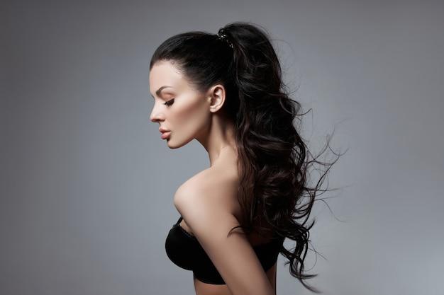 Sexy modefrau mit langen haaren, lockiges starkes haar eines brünetten mädchens in dessous.