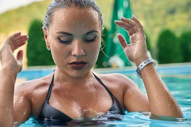 Sexy model beim psing im pool des spa-resorts