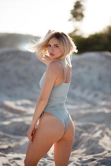 Sexy model im stylischen badeanzug, der barfuß auf sand zwischen leerem steinbruch spaziert. entzückende frau, die mit der hand ihr blondes haar berührt und nach unten schaut.