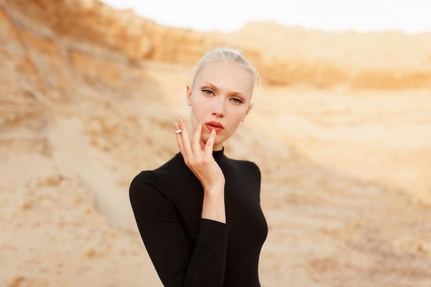 Sexy model mit blonden haaren und make-up, hält eine zigarette und raucht, blick in die kamera, gegen sandige karriere, bei sonnenuntergang.