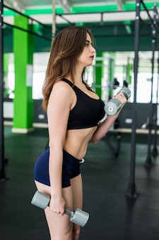 Sexy model mit brünetten haaren macht übungen im sportclub in schwarzer sportbekleidung