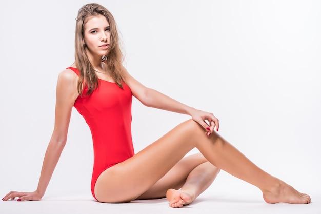 Sexy modell mit brünetten haaren sitzt auf dem boden gekleidet im roten badeanzug lokalisiert auf weißem hintergrund