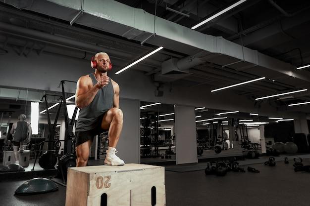 Sexy muskulöse männer, die die plattform für seine beine auf einem dunklen bunten hintergrund des fitnessstudios verwenden.