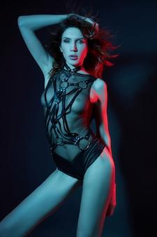Sexy nackte frau in einem gürtel im neonlicht. perfekte figur und brüste einer frau in unterwäsche, schöne haare