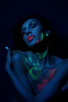 Sexy nackte frau in neonlicht, uv-farbe auf gesicht und körper der frau. perfekte figur und brüste einer frau, schöne haare