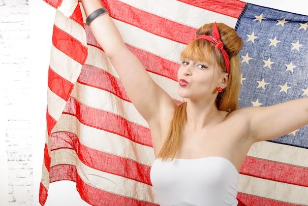 Sexy pin-up-frau, die eine amerikanische flagge hält.