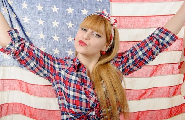 Sexy pin-up-mädchen isoliert hält eine amerikanische flagge