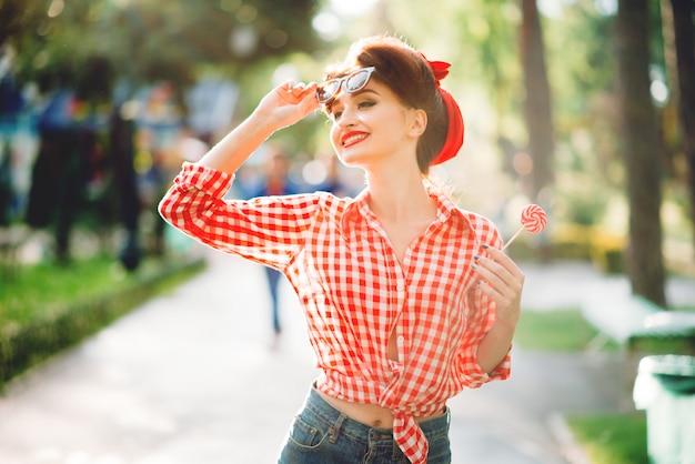 Sexy pin-up-mädchen mit lutscher in der hand geht in einem park, retro-amerikanische mode. attraktive frau im pinup-stil