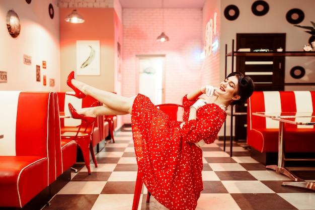 Sexy pin-up-mädchen mit make-up posiert im retro-café