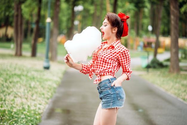 Sexy pinup-mädchen mit süßer zuckerwatte auf stick, retro-amerikanische mode. glamour-modell im pin-up-stil