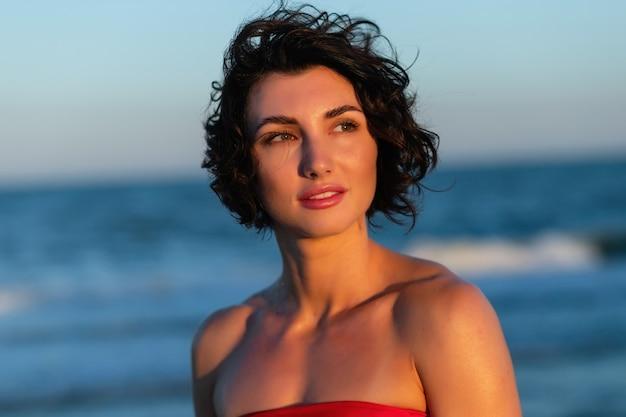 Sexy rücken einer schönen frau in einem roten badeanzug mit einem lächeln im gesicht glättet ihr haar vor dem hintergrund des meeres. mädchen in einem roten badeanzug vor dem hintergrund des meeres.