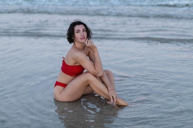 Sexy rückseite einer schönen frau im roten bikini auf seehintergrund. flache fokusaufnahme einer jungen attraktiven frau im roten bikini, die natürlich lächelt, während sie am strand sitzt