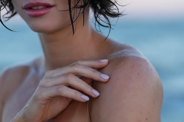 Sexy rückseite einer schönen frau im roten bikini auf seehintergrund. junges brünettes mädchen in einem roten badeanzug steht während eines heißen sommers im wasser. strandfoto vom meer aus.