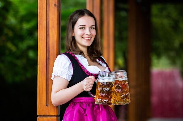 Sexy russische frau im bayerischen kleid, das bierkrüge hält