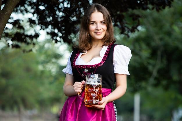 Sexy russische frau im bayerischen kleid, das bierkrüge hält Premium Fotos