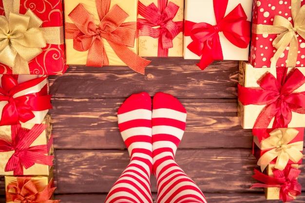 Sexy sankt-frauenbeine und -geschenkboxen. weihnachtsferienkonzept. ansicht von oben