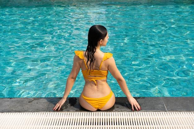 Sexy schlanke mädchenruhe am swimmingpool.