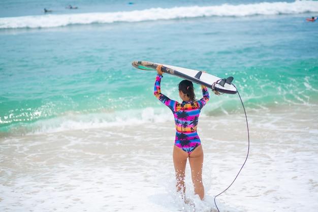 Sexy schlankes mädchen mit surfbrett am tropischen sandstrand. gesunder aktiver lebensstil in der sommerberufung.