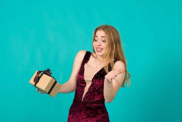 Sexy schneemädchenkostüm auf blauem hintergrund im studio, kaukasische dame im kleid, das an der kamera aufwirft. kopieren sie platz für text.