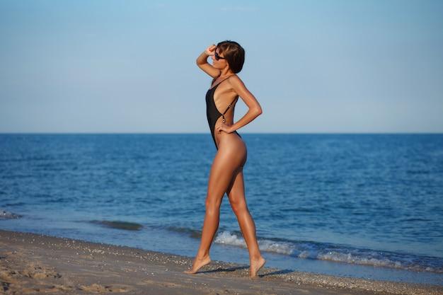 Sexy schöne frau im schwarzen kleinen bikini auf seehintergrund