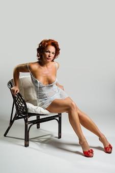 Sexy schöne frau mit dem roten haar, das auf einem stuhl sitzt