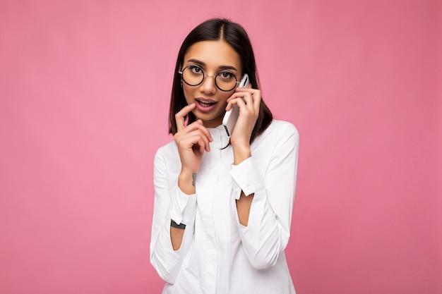 Sexy schöne junge brünette frau mit weißer bluse und optischer brille, die isoliert über rosafarbenem hintergrund steht und am handy spricht, in die kamera schaut und denkt.