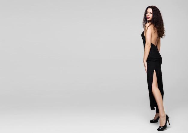 Sexy schöne modefrau, die schwarzes kleid trägt