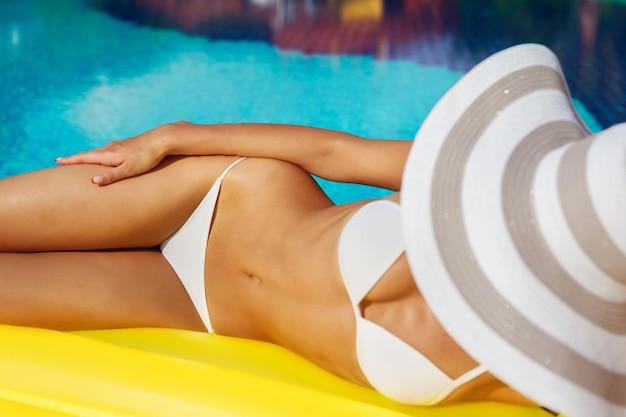 Sexy schönes frauenmodell im bikini entspannt sich im schwimmbad