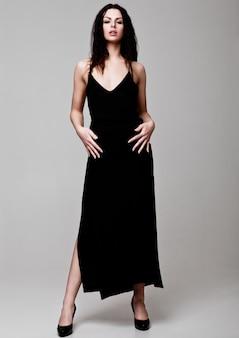 Sexy schönes mode-modell, das schwarzes kleiderschönen körper auf grau trägt