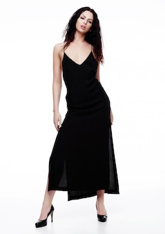 Sexy schönes mode-modell, das schwarzes kleiderschönen körper auf weiß trägt