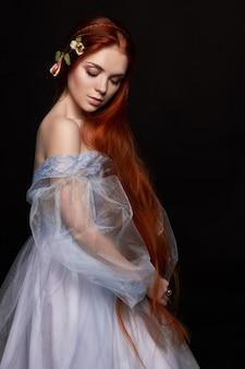 Sexy schönes rothaariges mädchen mit langen haaren im kleid baumwolle retro. frauenporträt. tiefe augen. natürliche schönheit, saubere haut, gesichtspflege und haare. starkes und dichtes haar. blume