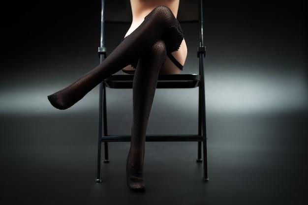 Sexy silikonpuppenfrau in der schwarzen spitzewäsche und in den strümpfen