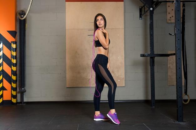 Sexy sportlerin in schwarzen leggings mit transparentem stoff und in rosa turnschuhen steht im fitnessstudio und hält ein seil